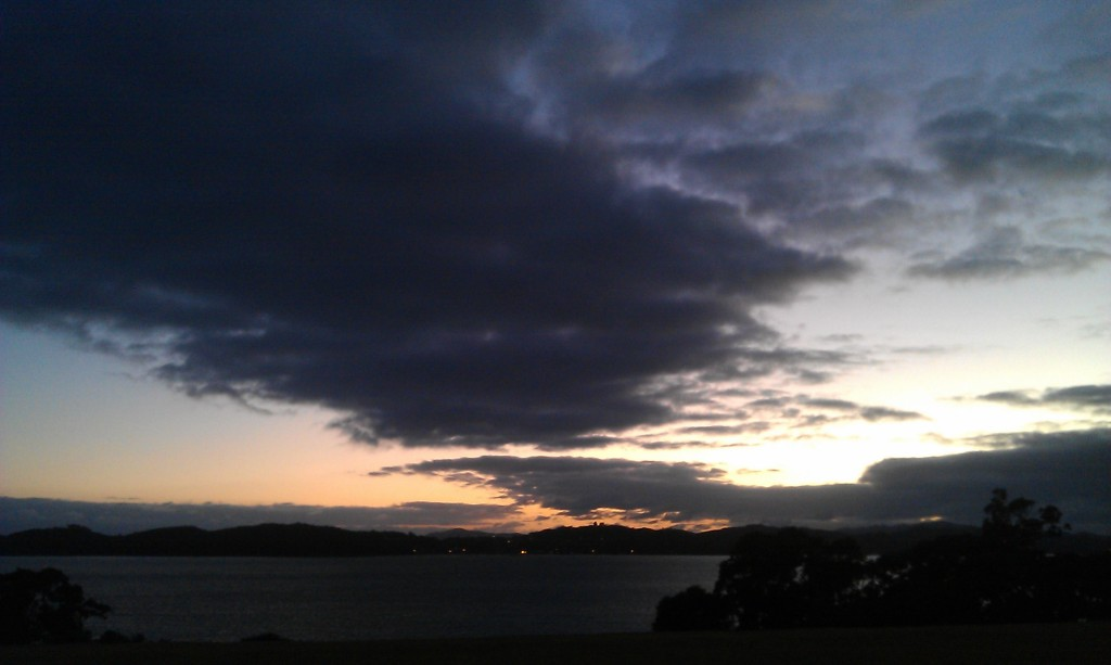 View of the sun rising over the water from the Treaty Grounds, Waitangi, New Zealand